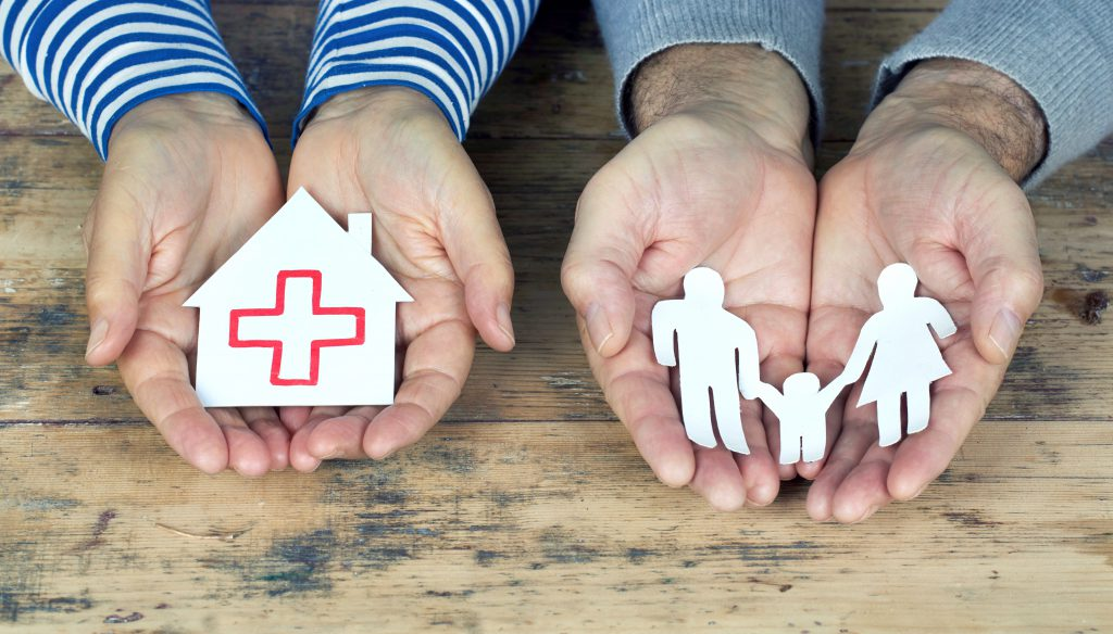 Hände halten Papierfamilie und Papierhaus mit roten Kreuz